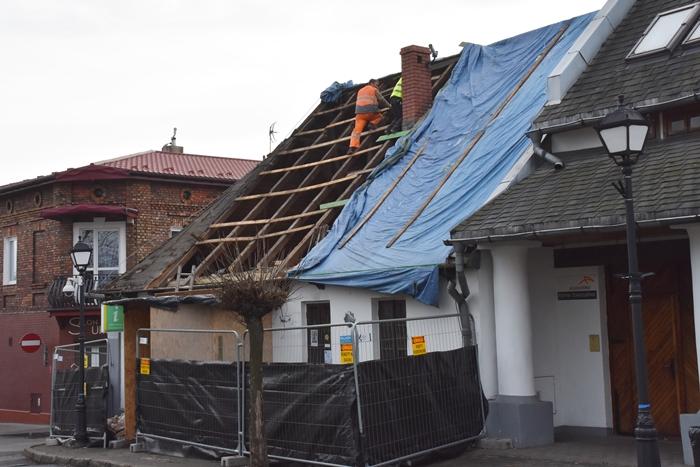 Robotnicy pracujący przy zdjętym częściowo dachu budynku