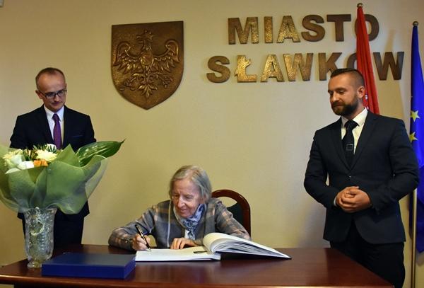 Przedstawiciele władz miasta i wdowa po poecie dokonująca wpisu do pamiątkowej księgi