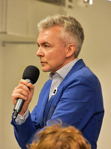 Przedstawiciel publiczności zadający pytanie uczestnikom debaty