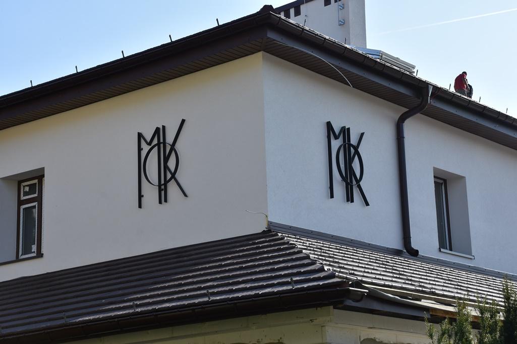 Zbliżenie na narożnik pierwszego piętra z odnowioną elewacją i logotypem MOK