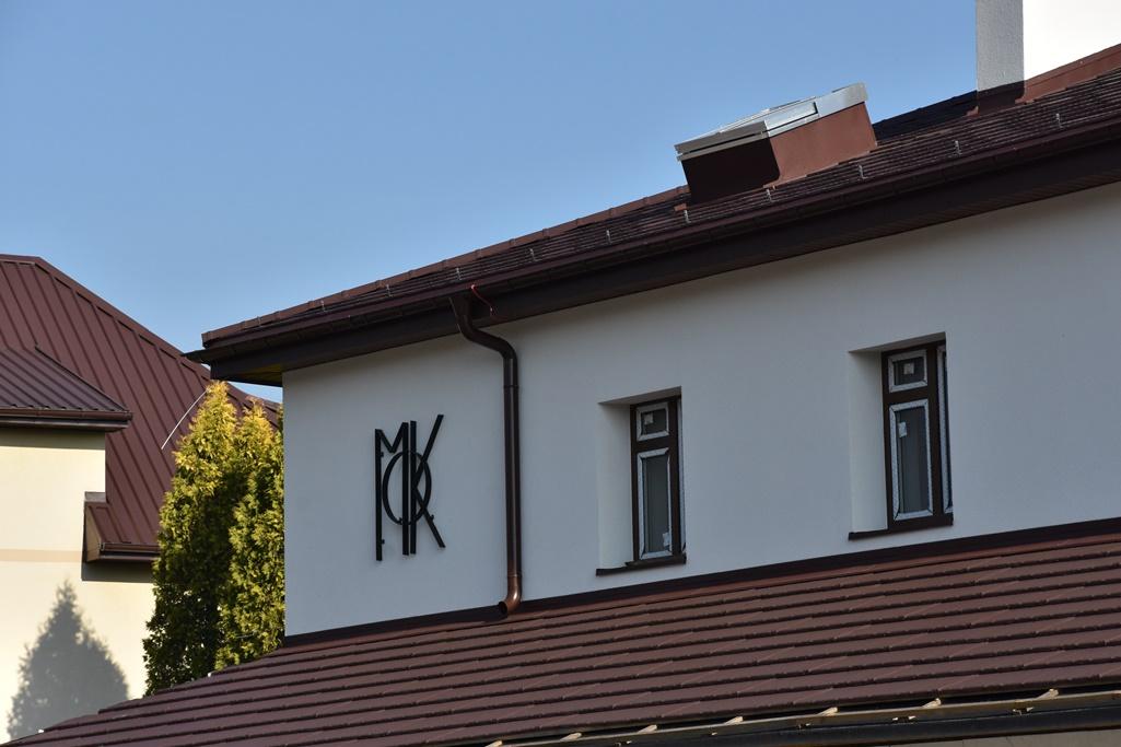 Widok z zewnątrz na elewację pierwszego piętra z brązową dachówką, wymienioną stolarką okienną