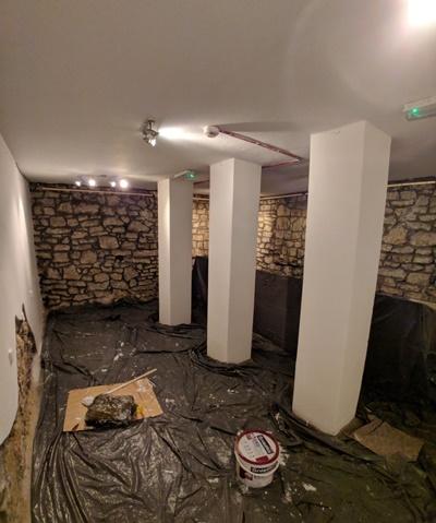 Widok na pomieszczenie w pwnicy. Widoczne betonowe kolumny, na podłodze czarna folia zabezpieczająca. Pomieszczenie w trakcie remontu