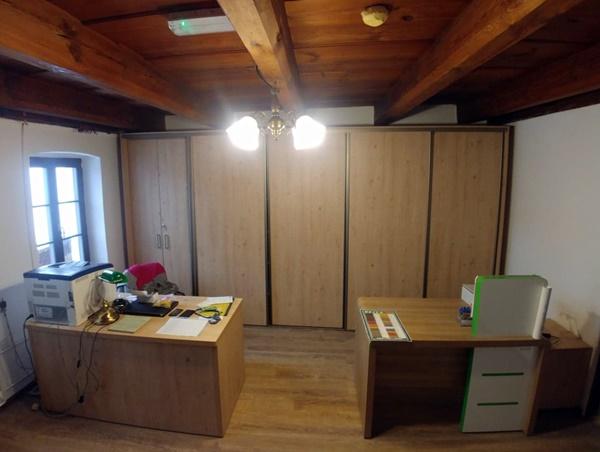 Zdjęcie przedstawia pomieszczenie biurowe, wykonane z wysokosści. Po prawej i lewej stronie widoczne biurka i krzesła, z tyłu widoczna szafa trzyczęściowa