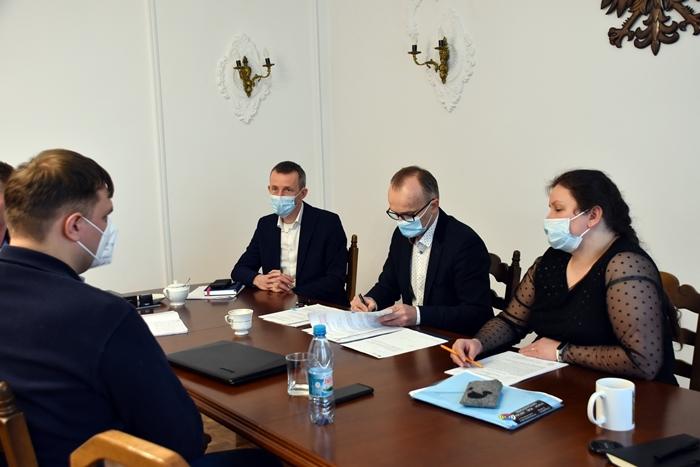 Zdjęcie przedstawia osoby siedzące przy stole w sali. Jedna z osób - burmistrz miasta podpisuje umowę