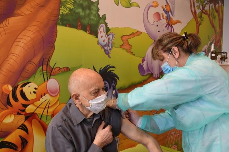 Na zdjęciu widoczne wnętrze gabinetu zabiegowego. Na ścianie kolorowe rysunki bajkowych. Na pierwszym planie siedzi mężczyzna, obok niego stoi pielęgniarka wykonująca mu szczepienie.