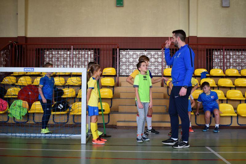 Na zdjęciu widoczna grupa dzieci wraz z trenerem podczas zajęć