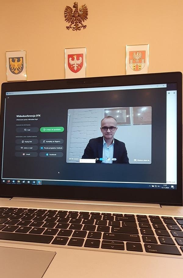 Zdjęcie przedstawia ekran laptopa, na którym znajduje się otwarte okno programu do wideokonferencji. W oknie programu widoczny burmistrz Sławkowa biorący udział w wideokonfernencji.