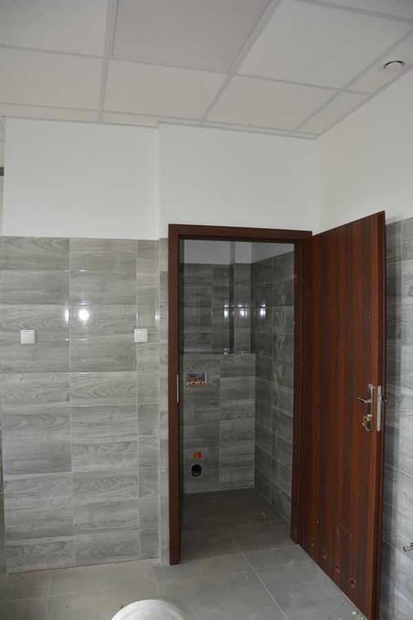 Widok na wejście do wyremontowanej toalety. Widoczne uchylone drzwi, za nimi toaleta