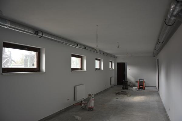Odnowiony korytarz, widoczne rury w obudowie, po lewej stronie prostokątne okna