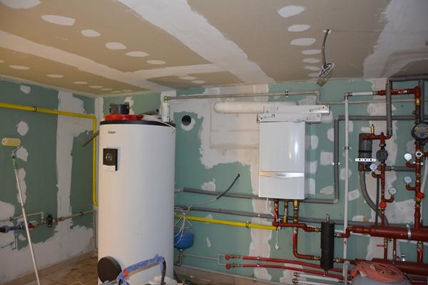 Widok pomieszczenia z urządzeniami do podgrzewania wody. Widoczne rury, na ścianach ślady gipsu