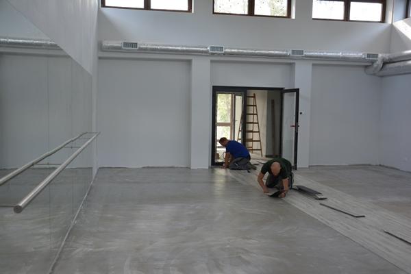 Wnętrze budynku. Dwaj pracownicy wykonują prace związane z parkietem. Z tyłu widoczna drabina