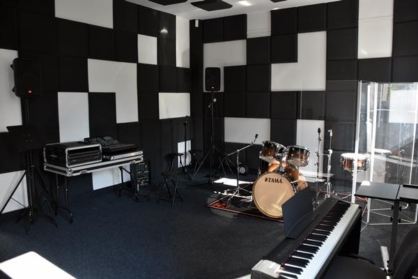 Zdjęcie przedstawia salę muzyczną, ściany wyłożone materiałami dźwiękochłonnymi. Widoczne sprzęty w postaci sprzętu mikserskiego i perkusji.