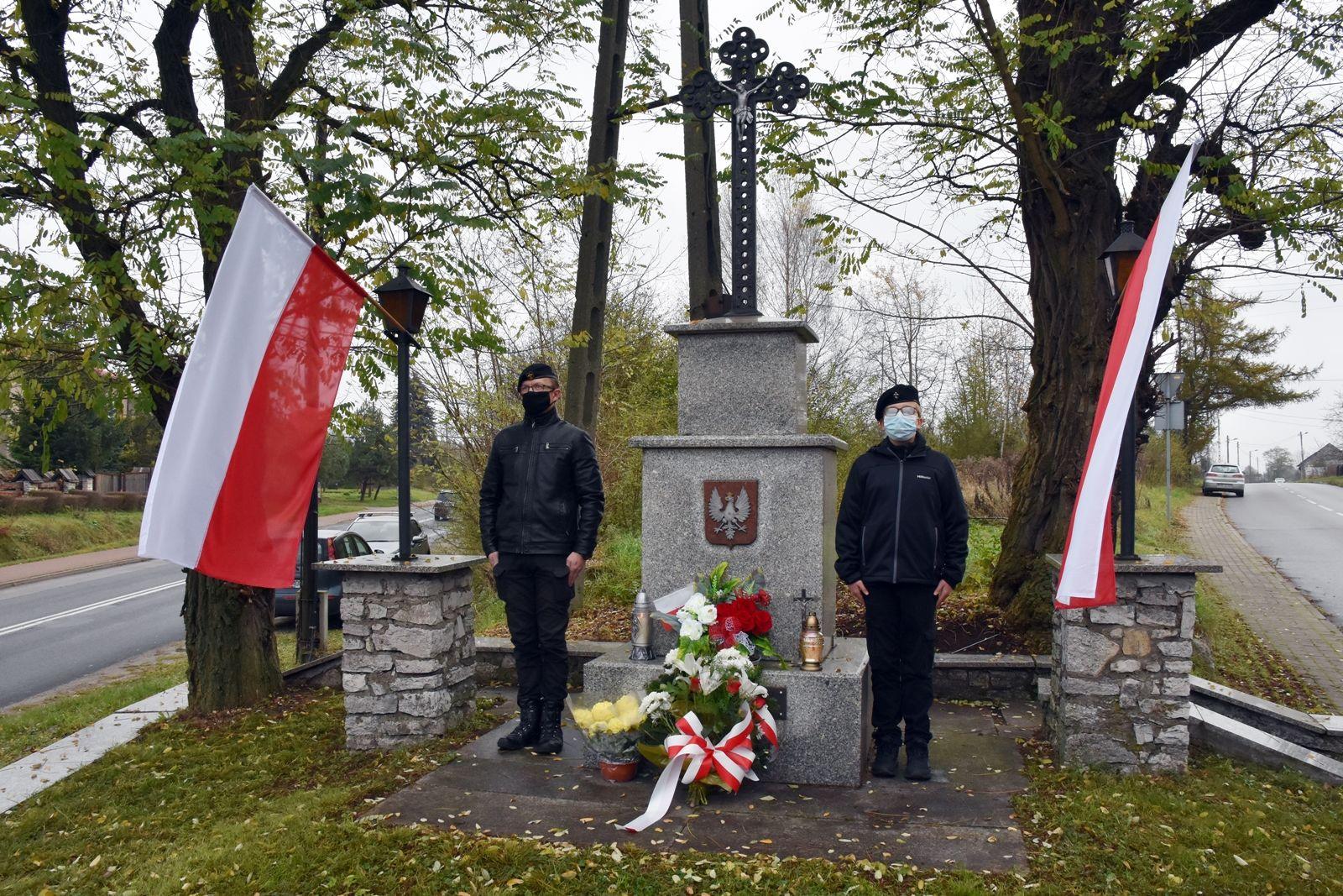 Na zdjęciu widoczny pomnik i dwóch harcerzy stojących na warcie. Obok pomnika biało-czerwone flagi.