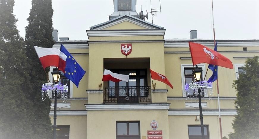 Budynek ratusza i latarnie przed ratuszem przyozodobione flagami Polski, Sławkowa i Unii Europejskiej.